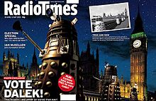 """A gatefold magazine cover, depicting a nighttime scene with four gold Daleks in the foreground, the railing of a bridge in the midground, and the Perpendicular Gothic towers of the Houses of Parliament and Big Ben in the background. The left half of the image contains the text """"Radio Times"""" in the top, and """"VOTE DALEK!"""" in the lower left. A small black-and-white photograph is superimposed on the upper left of the right side of the image; that photograph, taken from a slightly different angle, shows four Daleks crossing the same bridge, with the same building in the background."""
