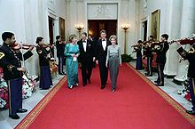 Long shot of two men flanked by two women walking down read carpet, as military band plays on either side