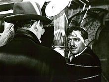 A screen capture from the film, showing a distraught Cesar tied up to a pole staring at Tony le Stephanoi who has his back to the camera.