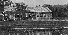 A large, low house, much like a farmhouse, overlooking a lake or river