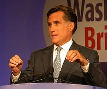 Mitt Romney speaking from a pulpit with both hands raised for emphasis