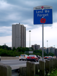 A sign beside a highway with the text Route of Heroes. In the space below is the text Lest we forget, and a red poppy below that.