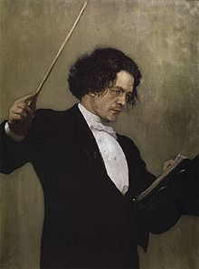 A middle-aged man with long dark hair, wearing a tuxedo and standing behind a music stand, waving a conductor's baton.