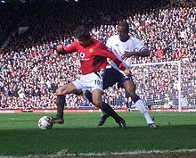 A photograph of two men playing football. The man on the left, who is wearing a red shirt, white shorts and black socks, is shielding the ball from the man on the right, who is wearing a white shirt, navy blue shorts and white socks with navy blue trim.