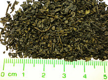 A pile of brownish-dark green dried leaf pieces, with a ruler for measurement. The pieces are generally round with diameters of 1 to 4 mm. Some pieces are rectangular, about 1 to 3 mm wide and 3 to 8 mm long.