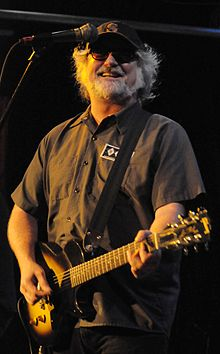 Scott McCaughey holding a guitar and smiling onstage