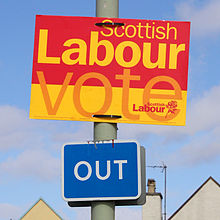 """A yellow, orange and red election sign reading """"Scottish Labour: Vote Scottish Labour"""" attached to a lamppost above a road sign stating """"Out"""""""