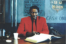 A middle-aged black man in a bright red suit sits at a dark brown desk against a backdrop of a wall painted in various dull shades of blue. His bejeweled hands are folded, and he is frowning with eyes focused off-camera to his left.