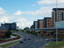 The start of the Sheffield Parkway, as viewed from Park Square, where it meets the City Centre. The road, in the centre, is six lanes wide and leads towards the Parkway Edge development (left-centre) where the road meets the Inner Ring Road. To the left is the Sheffield Supertram viaduct and beyond that a new apartment complex.