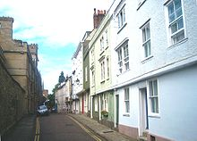 A narrow road, pavements either side; on the left, a stone wall; on the right, a row of terraced three storey houses, the upper storeys overhanging the ground floor