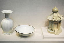 Three pieces of white porcelain. From left to right, a vase with a grooved, fat body, a short, thin stem, and small opening with a large flat rim extending from it, a simple bowl with a thin brown trim around the outside rim, and a container in the shape of a granary, with several viable support posts, a tiled roof, and a staircase leading to a door, all built into the piece.