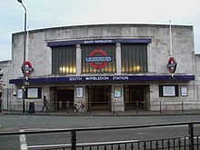 A curved white stone building with three glazed screens above a low three part entrance. The central screen features the London Underground logo in coloured glass (a red circle crossed by a horizontal blue bar carrying the UNDERGROUND name)