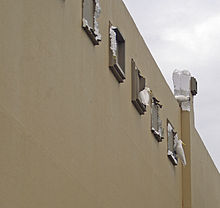 a number of white cockatoos are biting parts of the building wall, leaving chunks of polystyrene missing.