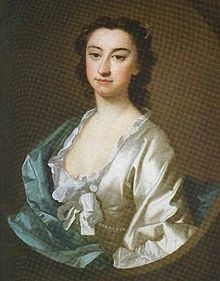 Dark-haired, dark-eyed woman with a large nose, wearing a low-cut white blouse