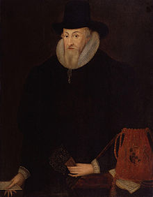Painting of a pale man with a pointed grey beard, in black Elizabethan dress, with a large white ruff and black hat. He is holding some papers in his left hand and a glove in his right. There is a red cloth bag with the royal coat of arms beside his right hand, in the foreground of the picture.