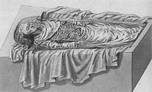 An open tomb seen from the side in a 45-degree angle from the ground. The corps, with his head to the left, is dressed in fine funeral attire, wears a coronet and holds a sceptre in each hand.