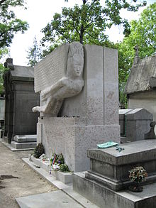 A large, rectangular, granite tomb. A large, stylised angel, leaning forward is carved into the top half of the front. There are a few flowers beside a small plaque a the base. The front is covered in red daubings and graffiti.