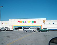 """Large, white Toys """"R"""" Us store under blue sky, with parking lot in front"""