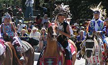 """""""Colour photograph of Tsuu T'ina children in traditional costume on horseback at a Stampede Parade in front of an audience"""""""