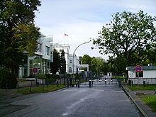 A street with a crossing green fence and a barrier with guard houses.