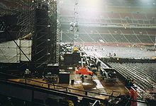 A side shot of a concert stage as a crew disassembles it at night. The stadium it is built in is empty and lit up.