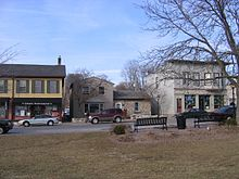 A row of three older buildings lines the far side of a street. On the near side is grass from a park with two park benches