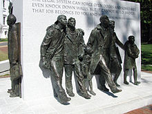 Bronze sculptures of seven figures marching stand around a large rectangular block of white engraved granite.