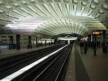 A cement-lined ceiling arches over an underground station. Two lines cross at right angles on separate levels.