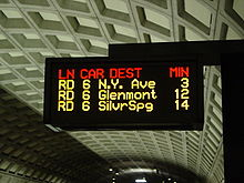 A electronic sign with multicolor text display mounted over a station platform.