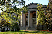 Gray stone building with large Doric columns and grassy foreground, framed by trees
