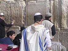 A man wearing a white robe with blue stripes stands in front of a stone wall.