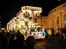 A large vehicle lit by multi-coloured lamps and carrying people in brightly-coloured coustumes in front of a large crowd on a darkened street.
