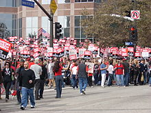 """A large group of people in front of a building, picketing with signs reading """"Writers Guild of America on Strike""""."""