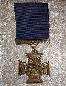 The obverse of the bronze cross pattée medal; showing the crown of Saint Edward surmounted by a lion with the inscription FOR VALOUR with a blue ribbon