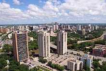 Skyline of an urban area with several tall skyscrapers surrounded by trees