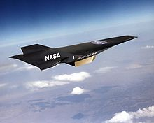 Artist's conception of black, wingless jet with pointed nose profile and two vertical stabilizers travelling high in the atmosphere.