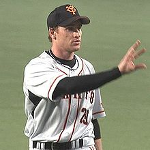A white man in a black baseball cap and a black long-sleeved shirt with a white baseball jersey over it extends his right hand.