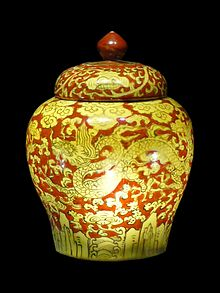 A porcelain jar with a red handle on top along with yellow dragons and clouds inscribed on a red background
