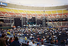 An elaborate concert stage, seen during the day inside a mostly empty stadium. The stage comprises several dark, rectangular structures. Fans are scattered throughout the floor seats, while the stadium seating is empty.