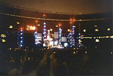 """An elaborate concert stage set bearing a logo that reads """"Zoo TV"""", set in a dark stadium. Towers reach into the nighttime sky, illuminated in blue with red warning lights on top."""