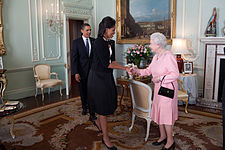 Michelle Obama and Elizabeth II shake hands and smile at each other as Barack enters the room in the background.