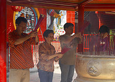A middle-aged man, an elderly woman, and two younger men pray in front of a censer vessel while holding red incense sticks. They are in a roofed structure painted in red.