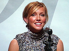 A smiling, blond woman in front of a microphone.