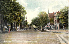 "A hand-tinted postcard image showing a cobblestone-paved, tree-lined street with many commercial buildings and some horse-drawn carriages. White script at the bottom left corner reads ""Main Street, East from White Street, Danbury, Conn."""