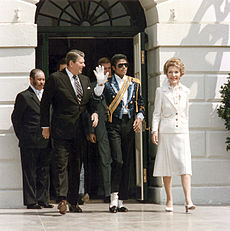 In the center of the photo four people can be seen. To the farthest left a medium skin colored man wearing a black suit with a white shirt can be seen. Second to the left a Caucasian man wearing a black suit with a white shirt and brown tie has his head turned to the right. To the right of the Caucasian male there is an African American man wearing a white shirt with a blue jacket that has a yellow strap across his chest. He is raising his right hand, which is covered with a white glove. To the farthest right, a Caucasian female with short blonde hair, who is wearing a white outfit, can be seen. In the background a cream colored building with an opened green door can be seen.