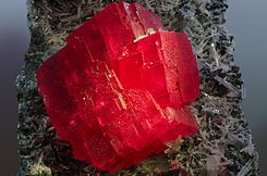 alt1=A mass of blocky, vivid red crystal extends from a dark rock covered with small, translucent white, rodlike crystals