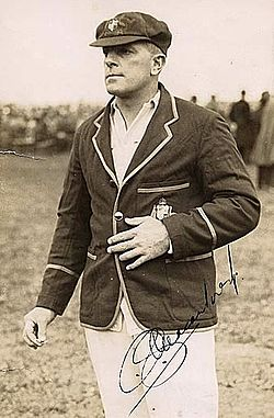 Stocky man in white cricket shirt and trousers with a blazer with the Australian coat of arms over the top of the shirt. His left hand is on his stomach and his right fingers are pressing something together, possibly a cigarette. The photo is signed by Macartney and there is a crowd of people in the background, and grass can be seen.