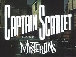 """In bold, white letters, the words """"Captain Scarlet"""" are superimposed on the backdrop of a derelict, night-time alleyway. Added at the bottom of the picture are more words, """"and the Mysterons"""", the last of which is in white, spiky lettering. The full title is thus revealed to be """"Captain Scarlet and the Mysterons""""."""