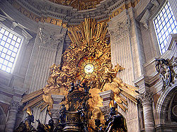"The chair-shaped bronze reliquary which holds the throne of St Peter is much larger than a normal chair, is ornate in shape and decorated with relief sculpture and gold leaf. The ""Gloria"" which surrounds a round window is a sculpture of clouds and sun-rays, surrounded by angels, the whole lot being covered in gleaming gold leaf."