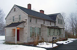 "A two-story gray wooden house with light green shutters seen in winter, with snow on the ground. A long wing with two brick chimneys projects towards the left from a higher rear section. At lower right is a black mailbox with ""5Ave"" on it next to a clear paved driveway"
